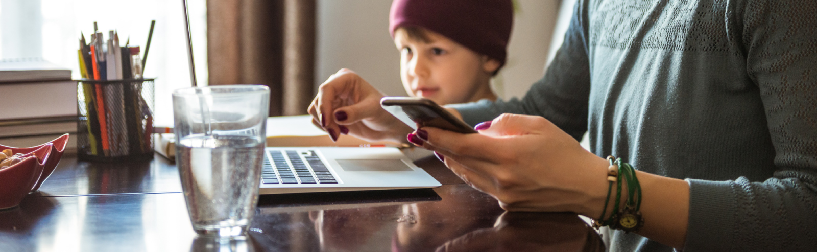 Man in front of laptop, holding phone with little boy beside him